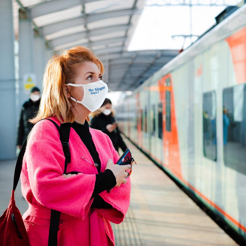 Frau mit MCS-Alltagsmaske wartet am Bahngleis